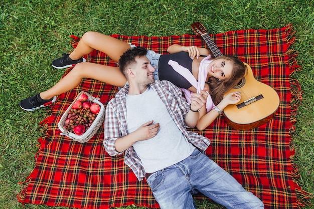 Jonge mooie paar liggen op het deken tapijt en kijken elkaar in het deken tapijt en meisje op zoek naar de camera Premium Foto
