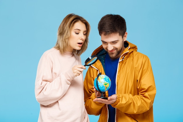 Jonge mooie paar poseren over blauwe muur met vergrootglas en wereldbol Gratis Foto