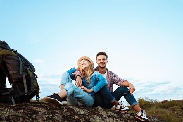 Jonge mooie paar reizigers genieten van uitzicht op canyon, glimlachend Gratis Foto