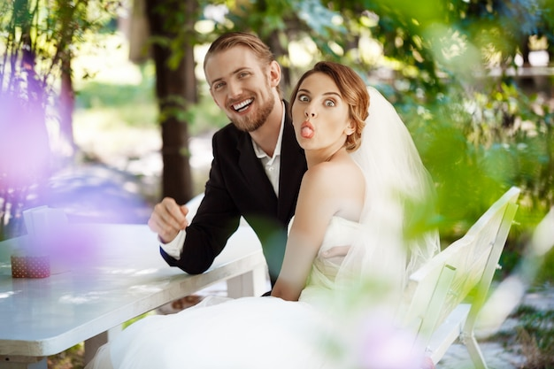 Jonge mooie pasgetrouwden gek, zittend in cafe buitenshuis. Gratis Foto