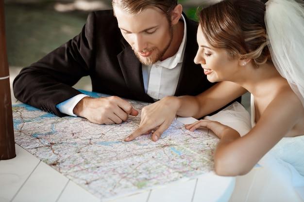 Jonge mooie pasgetrouwden glimlachen, kiezen voor huwelijksreis, kaart kijken. Gratis Foto