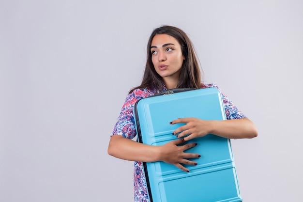 Jonge mooie reizigersvrouw die blauwe koffer koestert die opzij met positieve uitdrukking op gezicht kijkt die zich over witte achtergrond bevindt Gratis Foto