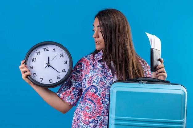 Jonge mooie reizigersvrouw die blauwe koffer met kaartjeskaartjes en klok in de hand houden die het verward status over blauwe achtergrond bekijken Gratis Foto