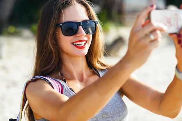 Jonge mooie reizigersvrouw die foto's maakt op zonnig strand, alleen reist met rugzak in warm tropisch land, casual outfit, fitnesslichaam, avontuurlijke stemming. Gratis Foto