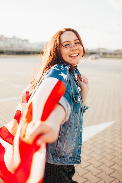 Jonge mooie roodharige vrouw gewikkeld met nationale vlag van de verenigde staten over zonneschijn. Premium Foto