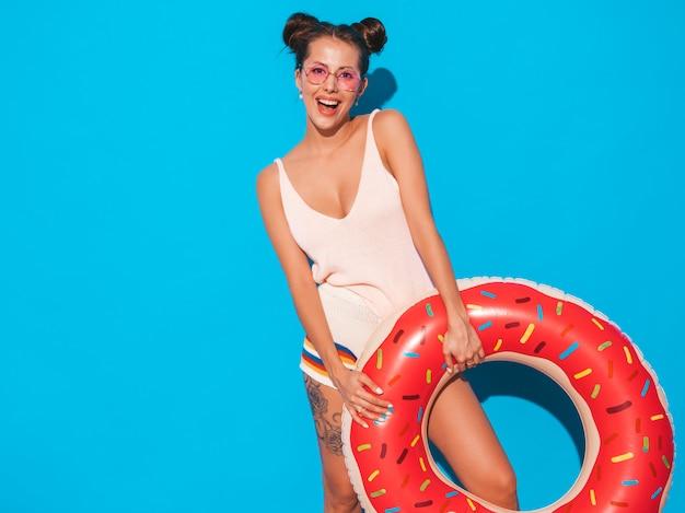 Jonge mooie sexy glimlachende hipster vrouw in zonnebril. met donut lilo opblaasbaar matras. Gratis Foto