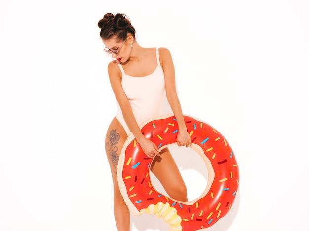 Jonge mooie sexy glimlachende hipster vrouw met rode lippen in zonnebril met de opblaasbare matras van doughnutlyo Gratis Foto