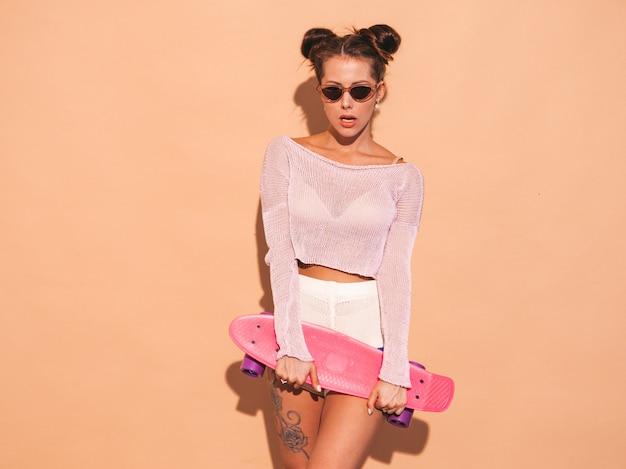 Jonge mooie sexy lachende hipster vrouw in zonnebril. trendy meisje in zomer gebreid vest onderwerp, shorts. positieve vrouw gek met roze cent skateboard, geïsoleerd op beige muur. twee hor Gratis Foto