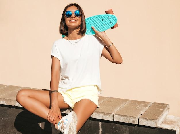 Jonge mooie sexy lachende hipster vrouw in zonnebril. trendy meisje in zomer t-shirt en korte broek. positieve vrouw met blauwe cent skateboard poseren op de straat achtergrond Gratis Foto