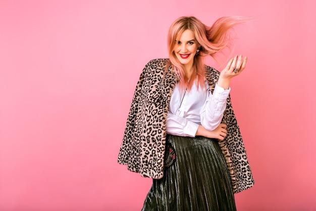 Jonge mooie sexy prachtige vrouw speelt met haar haren, avond sprankelende cocktail outfit en bont luipaard bedrukte trendy jas, roze achtergrond, positieve emoties dragen. Gratis Foto