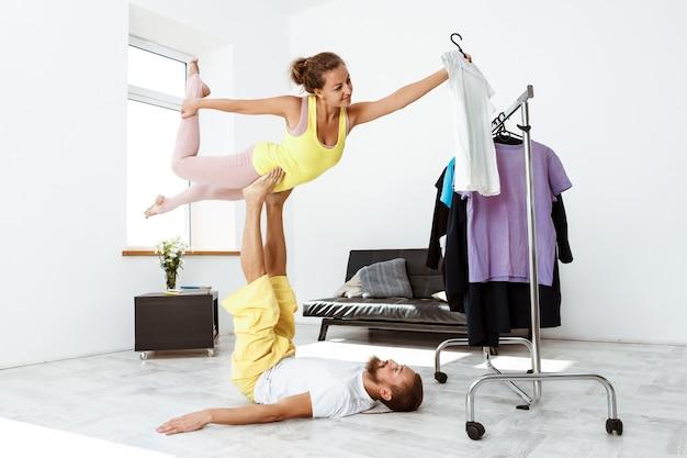 Jonge mooie sportieve paar yoga asana's van de opleidingspartner thuis. Gratis Foto