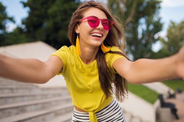 Jonge mooie stijlvolle lachende vrouw selfie foto maken in stadspark, positief, emotioneel, gele top, roze zonnebril, zomer stijl modetrend, lang haar, plezier dragen Gratis Foto