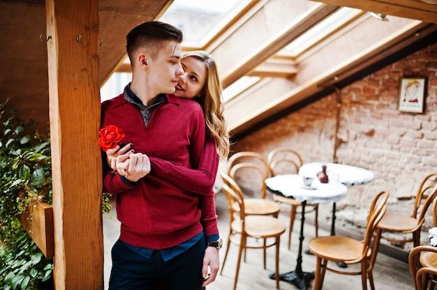 Jonge mooie stijlvolle paar in een rode jurk in liefdesverhaal in het vintage café met grote ramen op het dak Premium Foto