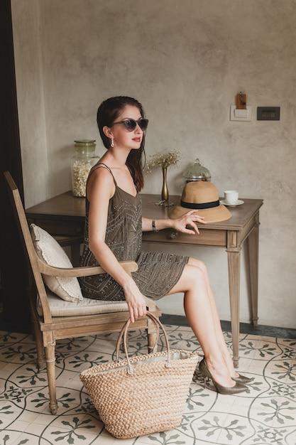 Jonge mooie stijlvolle vrouw in resort hotelkamer, zittend aan tafel, trendy jurk dragen, safaristijl, strooien hoed, glimlachen, gelukkig, zomervakantie, boheemse outfit, strandtas, zonnebril, benen Gratis Foto