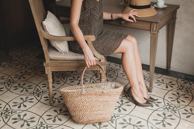 Jonge mooie stijlvolle vrouw in resort hotelkamer, zittend aan tafel, trendy jurk, safari stijl, strooien hoed, zomervakantie, bohemien outfit, strandtas, details close-up dragen Gratis Foto