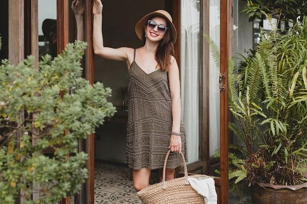 Jonge mooie stijlvolle vrouw in resorthotel, trendy jurk, safaristijl, strooien hoed, zomervakantie, boheemse outfit, strandtas, zonnebril dragen Gratis Foto