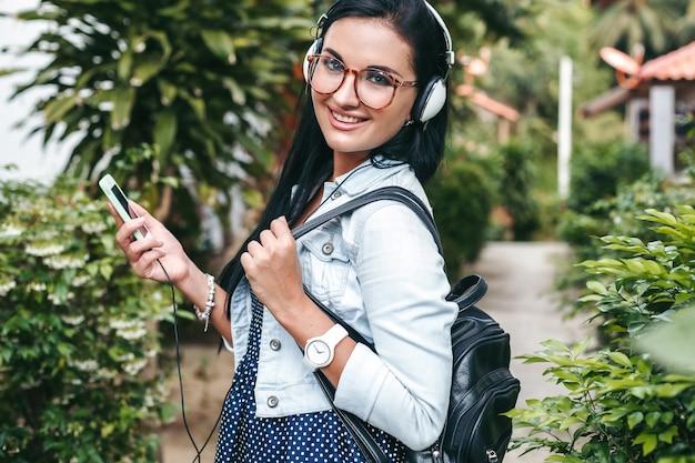 Jonge mooie stijlvolle vrouw met behulp van smartphone, hoofdtelefoon, bril, zomer, vintage denim outfit, glimlachen, gelukkig, positief Gratis Foto