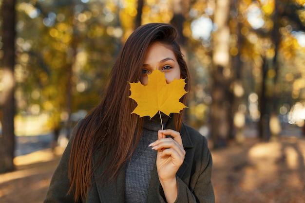 Jonge mooie stijlvolle vrouw met blauwe ogen in een modieuze jas, met een geel herfstblad in de buurt van het gezicht tijdens het wandelen in het park. de herfstportret van de close-up van gelukkig meisje Premium Foto