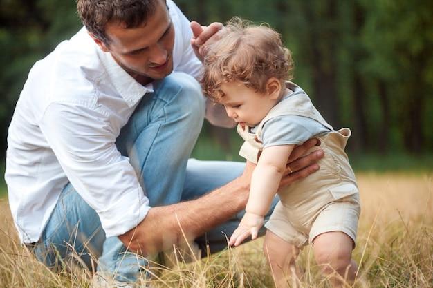 Jonge mooie vader, moeder en kleine peuterzoon tegen groene bomen Gratis Foto