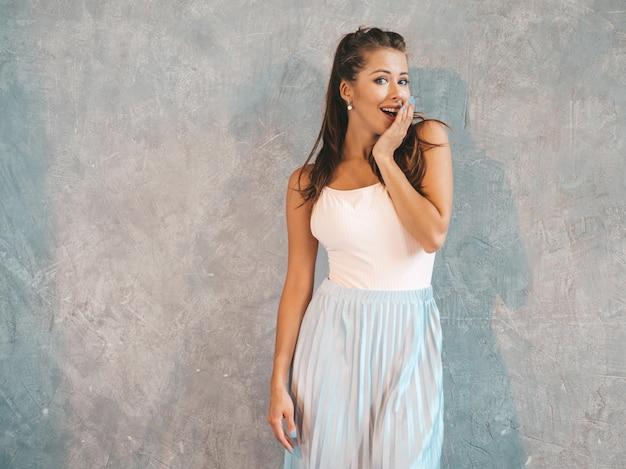 Jonge mooie verraste vrouw die met handen dichtbij gezicht kijkt. trendy meisje in casual zomerkleding. vrouw poseren in de buurt van grijze muur Gratis Foto