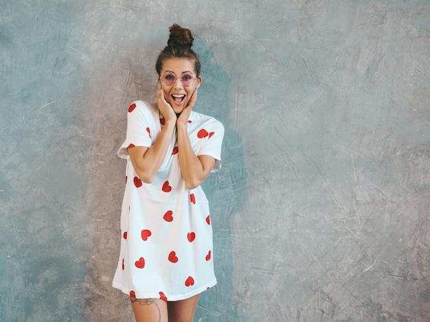 Jonge mooie verraste vrouw die met handen dichtbij mond kijkt. trendy meisje in casual witte zomerjurk. Gratis Foto
