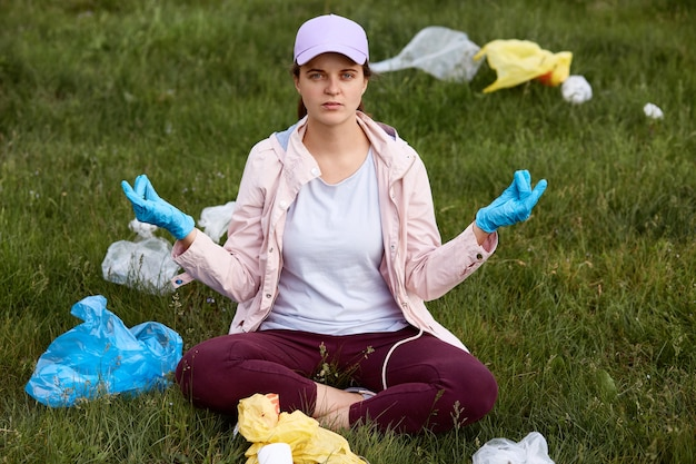 Jonge mooie vrijwilliger die zwerfafval opraapt in park, moe en boos is, probeert te ontspannen, in lotus houding op gras zit, camera kijkt, vrijetijdskleding draagt. Gratis Foto
