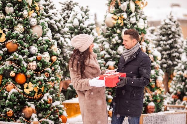 Jonge mooie vrolijke paar het vieren kerstmis in de stadsstraat en het geven van cadeau aan elkaar. Premium Foto
