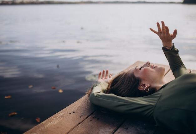Jonge mooie vrouw die aan het meer ligt Gratis Foto