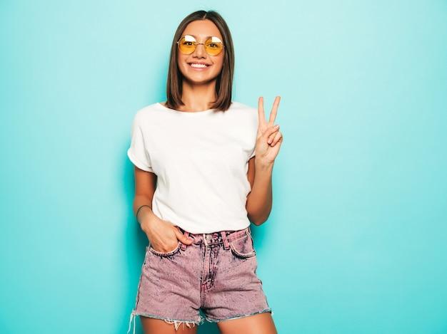 Jonge mooie vrouw die camera bekijkt. trendy meisje in casual zomer wit t-shirt en jeans short in ronde zonnebril. positieve vrouw toont gezichtsemoties. model geïsoleerd op blauw toont vredesteken Gratis Foto