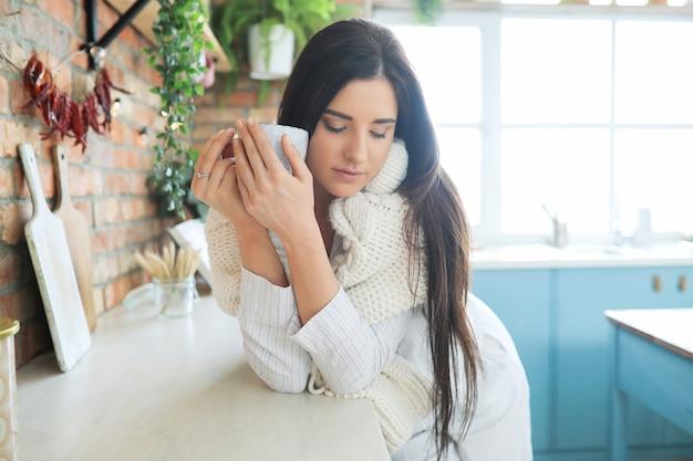 Jonge mooie vrouw die een warme drank in de keuken drinkt Gratis Foto