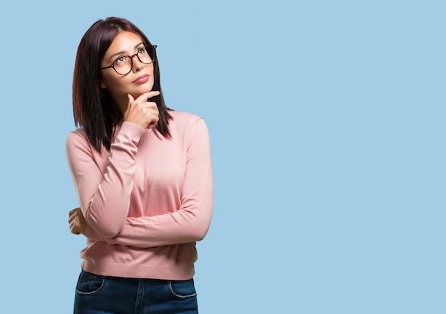 Jonge mooie vrouw die en omhoog kijkt denkt, verward over een idee Premium Foto