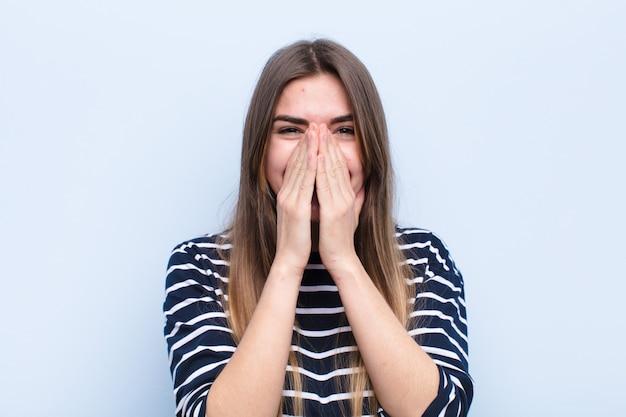 Jonge mooie vrouw die gelukkig, vrolijk, gelukkig en verrast bedekkend mond met beide handen tegen zachte blauwe muur kijkt Premium Foto
