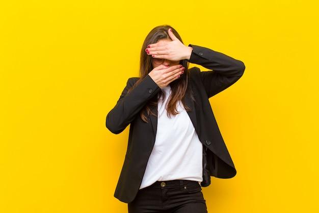 Jonge mooie vrouw die gezicht behandelt met beide handen die nee zeggen tegen de camera! afbeeldingen weigeren of foto's verbieden tegen de oranje muur Premium Foto