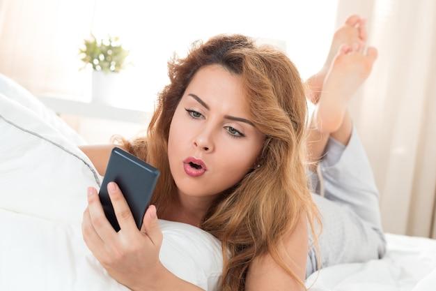 Jonge mooie vrouw die in haar bed legt en mobiele telefoon bekijkt. ochtend tijd. schokkend nieuws of een laat concept. Premium Foto