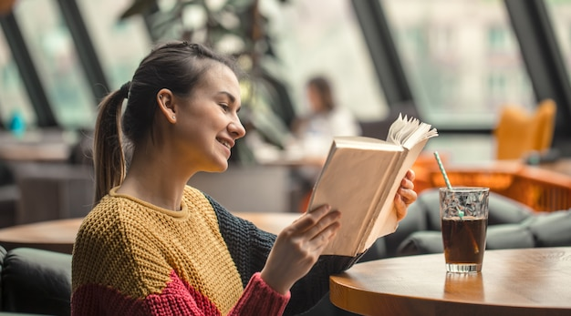 Jonge mooie vrouw die in oranje sweater interessant boek in koffie lezen Gratis Foto