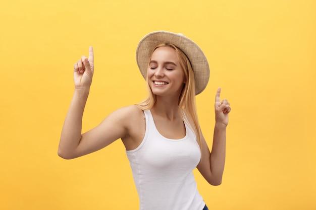 Jonge mooie vrouw die in studio dansen die op gele achtergrond wordt geïsoleerd Premium Foto