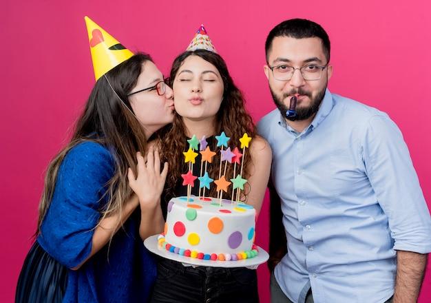 Jonge mooie vrouw die met krullend haar verjaardagstaart met haar de partijconcept van de vriendenverjaardag houdt over roze Gratis Foto