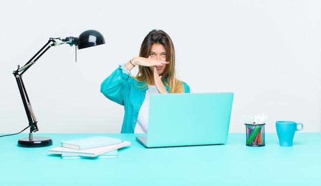 Jonge mooie vrouw die met laptop werkt die ernstig kijkt Premium Foto