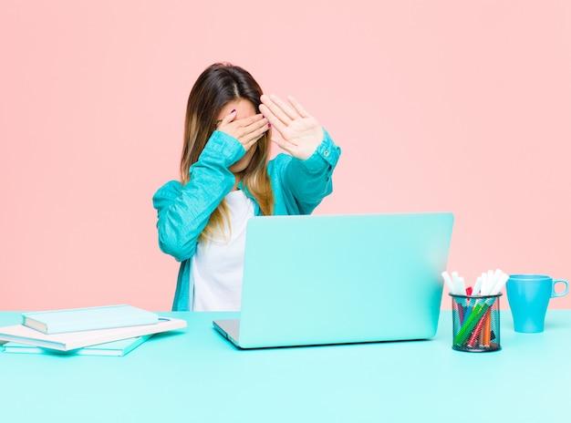 Jonge mooie vrouw die met laptop werkt die gezicht behandelt Premium Foto