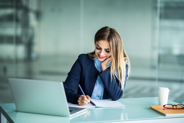 Jonge mooie vrouw die met laptop werkt en notities maakt op een desktop op kantoor Gratis Foto