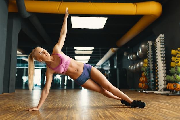 Jonge mooie vrouw die met persoonlijk gewicht in een moderne gymnastiek uitwerkt Gratis Foto