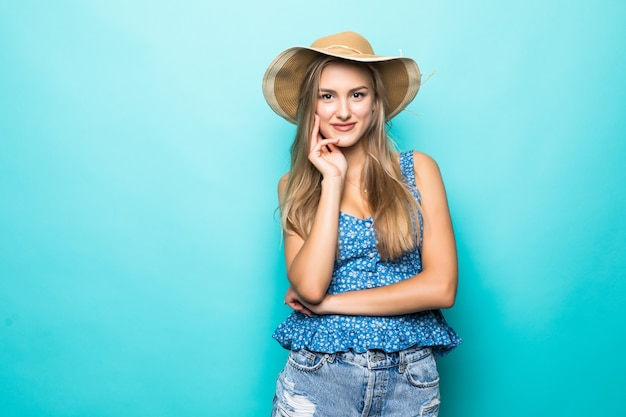Jonge mooie vrouw die met strohoed en gelukkig op blauwe achtergrond glimlacht Gratis Foto