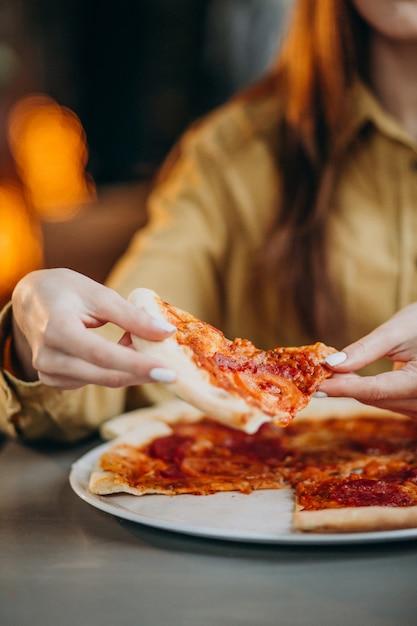 Jonge mooie vrouw die pizza eet bij een bar Gratis Foto