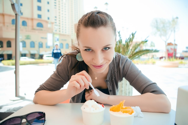Jonge mooie vrouw die roomijs eet Gratis Foto