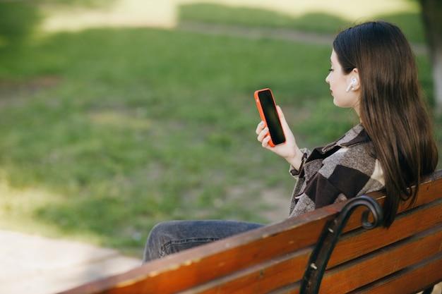 Jonge mooie vrouw die zich op een bank bevindt die de telefoon met behulp van Premium Foto