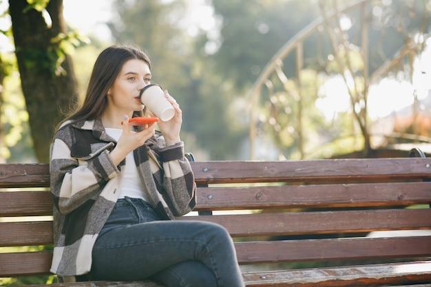 Jonge mooie vrouw die zich op een bank bevindt die laptop met behulp van Premium Foto