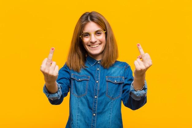Jonge mooie vrouw die zich provocerend, agressief en obsceen voelt, de middelvinger omdraait, met een rebelse houding over de gele muur Premium Foto