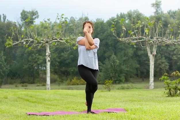Jonge mooie vrouw doet yoga oefening buitenshuis Gratis Foto