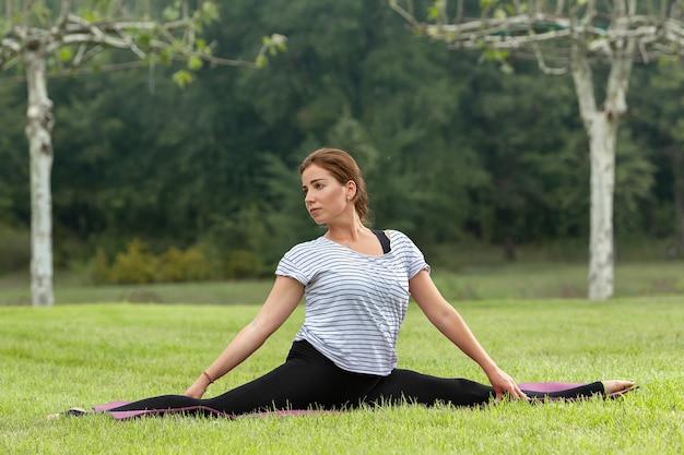 Jonge mooie vrouw doet yoga oefening in groen park Gratis Foto