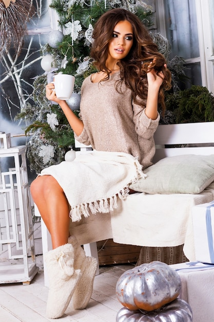 Jonge mooie vrouw dromen en drinken koffie of thee, genieten van kerstochtend, close-up portret van mooie dame in warme, gezellige kleren zittend op licht ingericht terras Gratis Foto
